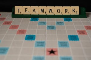 scrabble board game with the word teamwork