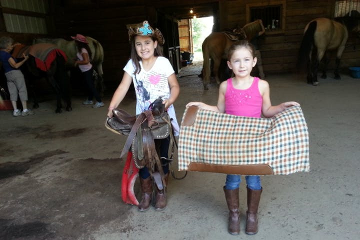 Two young girls holding saddle pads in a barn