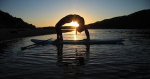woman doing sup yoga during sunset
