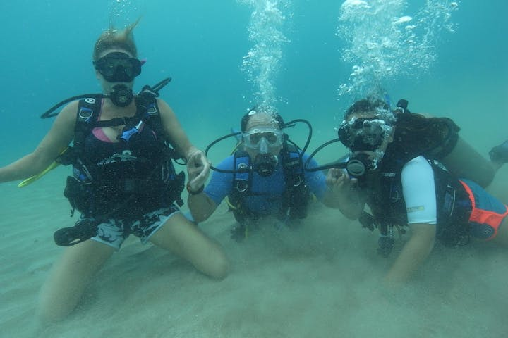Three scuba divers laying on the bottom of the ocean floor
