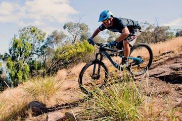 a man riding a bike down a dirt road