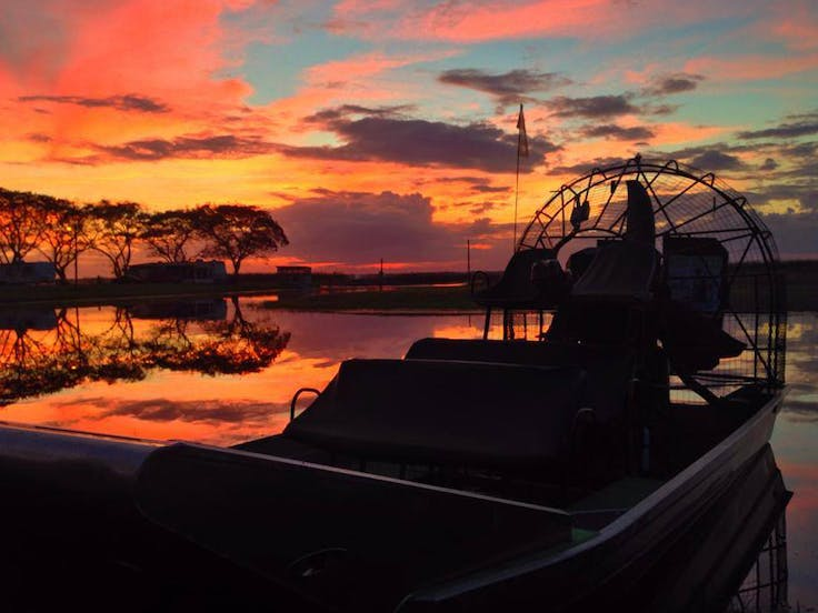 An airboat silhouette against a vibrant Florida sunset