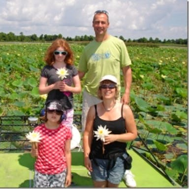 A group poses with water lilies in Lake Tohopekaliga