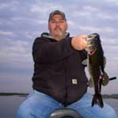 A fisherman holds a bass caught on Lake Toho