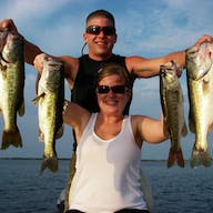 A man and a woman hold up bass they caught fishing
