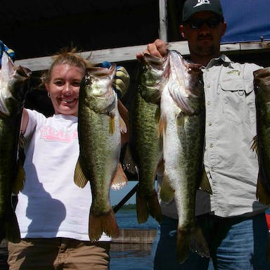Two people hold up largemouth bass they caught