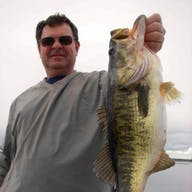 A man shows off a largemouth bass caught in Lake Toho