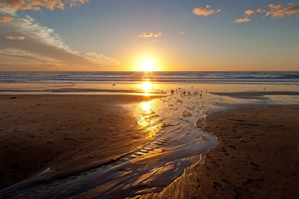 a sunset over a sandy beach