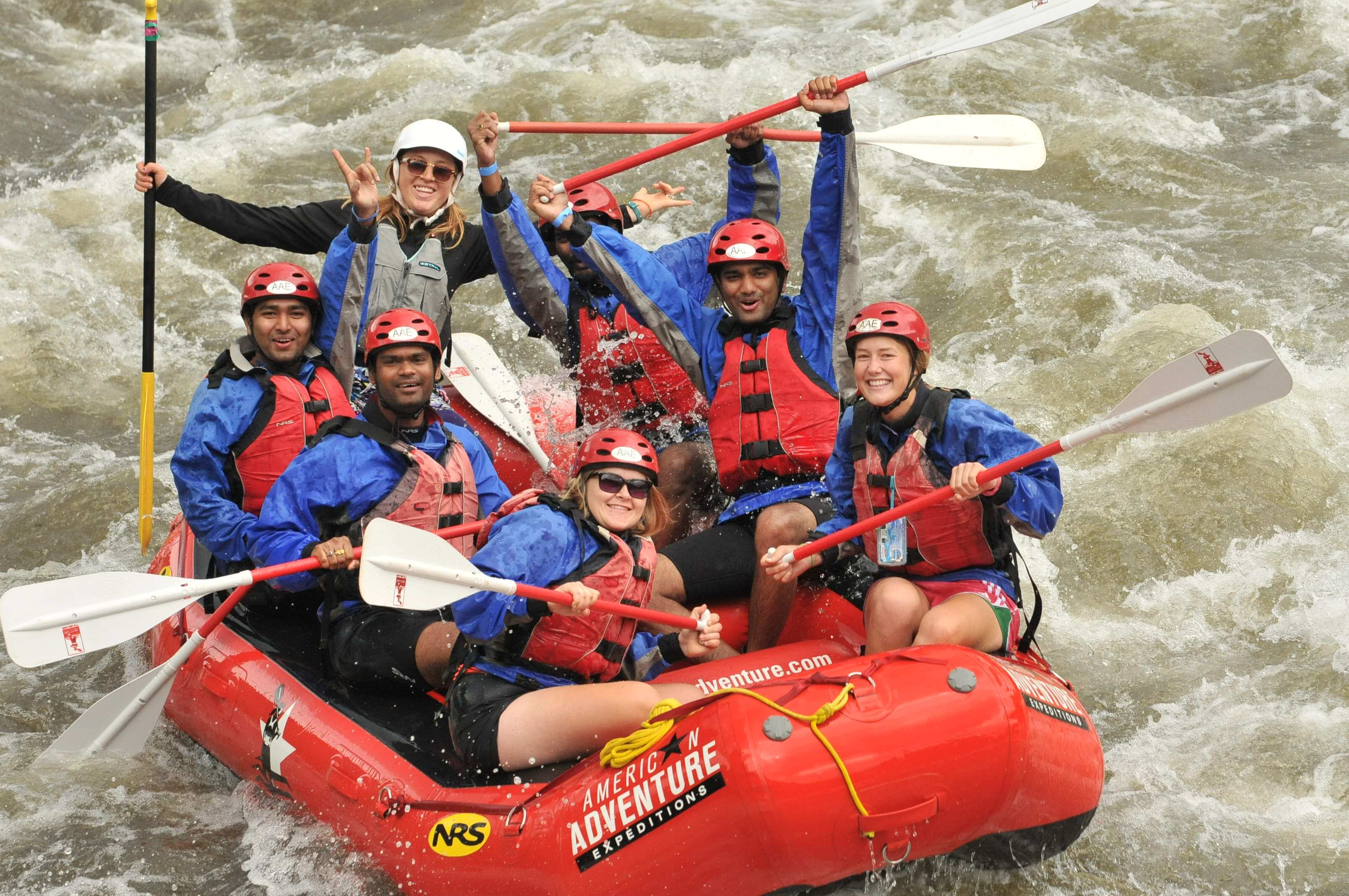 team poses on rafting during team building activity