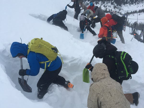 People digging in snow for avalanche safety practice