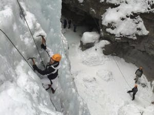 Solo ice climber climbing up cliff