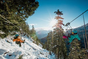 Two people ziplining in Whistler in Winter