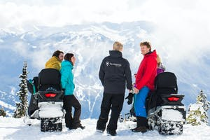 A group of people rest at the top of Whistler on snowmobiles.