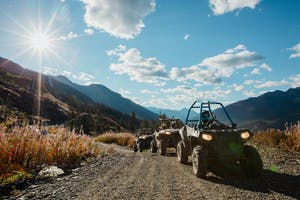 Line of RZR with mountains and sky in background
