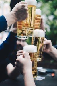 Focus on people holding pints of beer in cheers