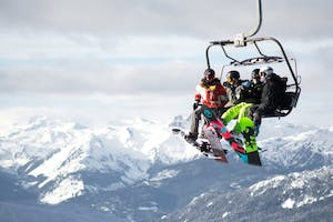 A few friends sit on a chair lift in Whistler