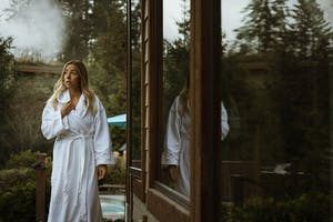 Woman outside a sauna in a bath robe in Whistler