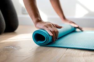 woman rolling up the yoga mat