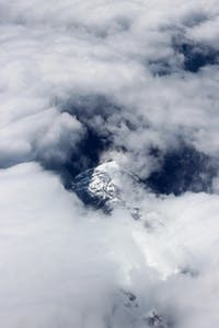 Clouds flowing over the top of a snowy mountain