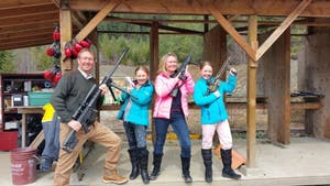parents pose with their children, holding guns, at the Whistler Gun Range