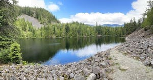 a rocky river with trees on the side of a lake surrounded by trees, Crater Rim Loggers lake, whistler