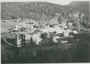 a vintage photo of a boat and mill, Parkhurst Ghosttown next to a body of water