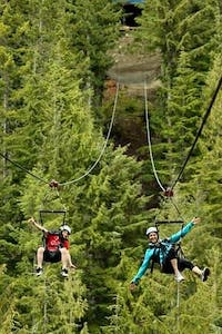 Two friends sore through the forests on Superfly Zipline