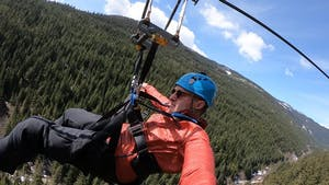 Adult takes a selfie while on a zipline in Whistler.