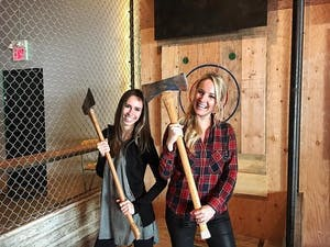 Two women in plaid hold axes at Forged Axe Throwing in Whistler