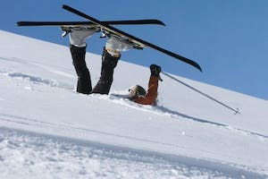 A skier upside-down on the snow