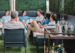 a group of men on an outdoor patio, champagne and beer glasses.