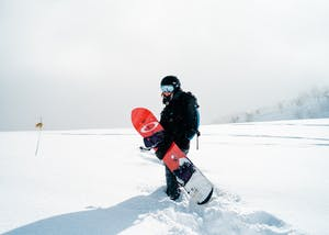 Woman standing in powder with snowboard.