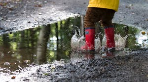 Kid in red rubber boots, splashing in the rain
