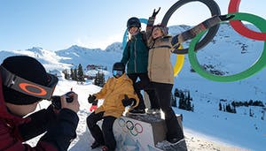a group of friends poses in front of the whistler olympic park rings