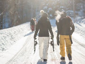 Two people walk a trail with snowshoes