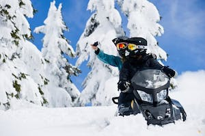 Two people on a snow mobile, Canadian Wilderness Adventures