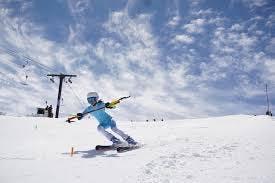 Ski racing sisterhood a person riding skis down a snow covered slope
