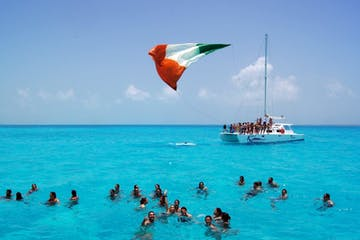 people on beach with mexican flag on boat
