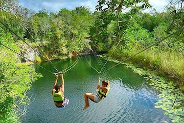 Two people ziplining over river