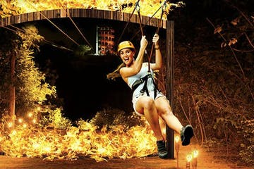 Person ziplining with fire in the background