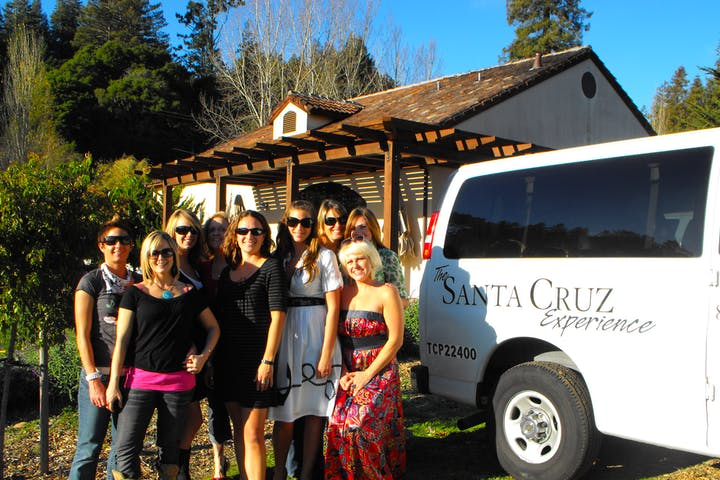 Wine tour participants posing near shuttle van