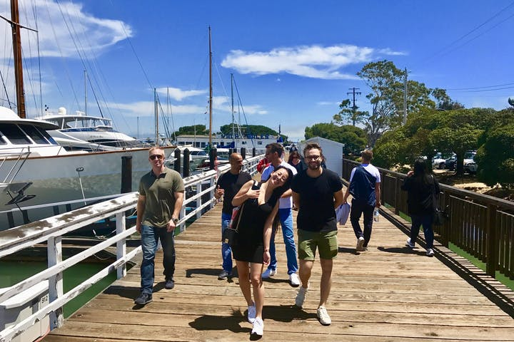 Group of tourists walking on a dock in a boatyard in Sausalito, CA