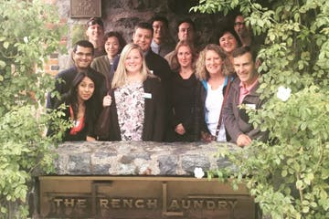 Group of people from a private Gourmet Food & Wine Tour posing for a photo at The French Laundry in Napa County, CA