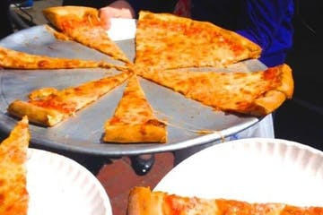 People taking slices of cheese pizza at a restaurant in Sausalito, CA