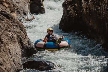 a person in a raft on top of a rock