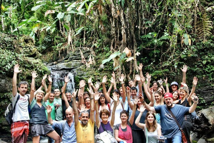 A tour group in El Yunque forest by a waterfall