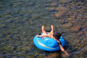 man reaching for something in the water while tubing
