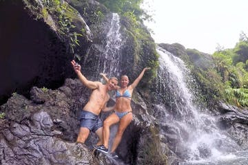A couple smiling on the rocks near the jungle waterfall