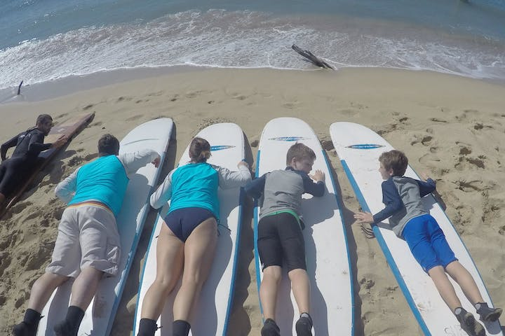 A family on the beach learning how to surf