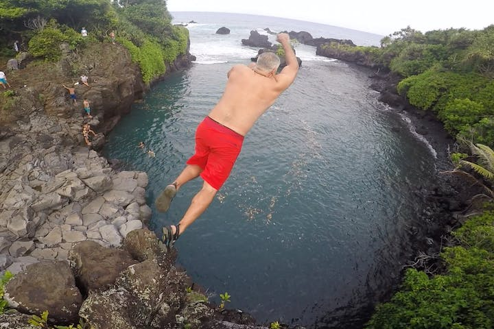 An older gentleman in swim trunks jumping off a cliff into a pool of water in Hana